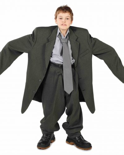 little boy in big grey man's suit and boots nads at sides isolated on white background