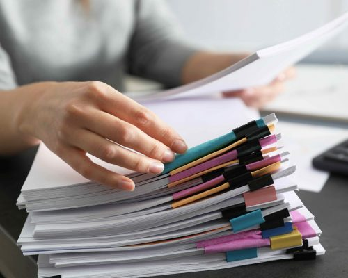 Office employee working with documents at table, closeup