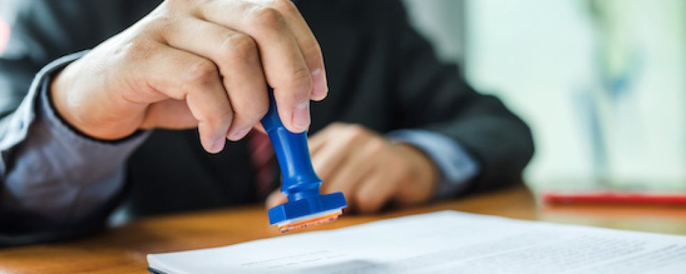 Businessman stamping with approved stamp on document at meeting.